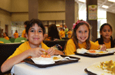 Image of two girls smiling while eating lunch in the cafeteria - Link to freed and reduced price meal income guidelines