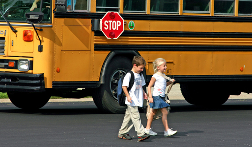 Children walking to school with school bus in background