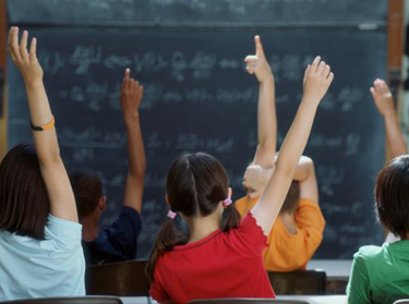 Children raising their hands in a classroom