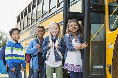 group of children waiting outside the school bus