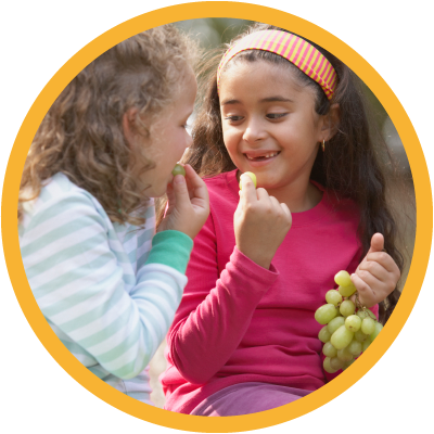 Two young children snacking on green grapes